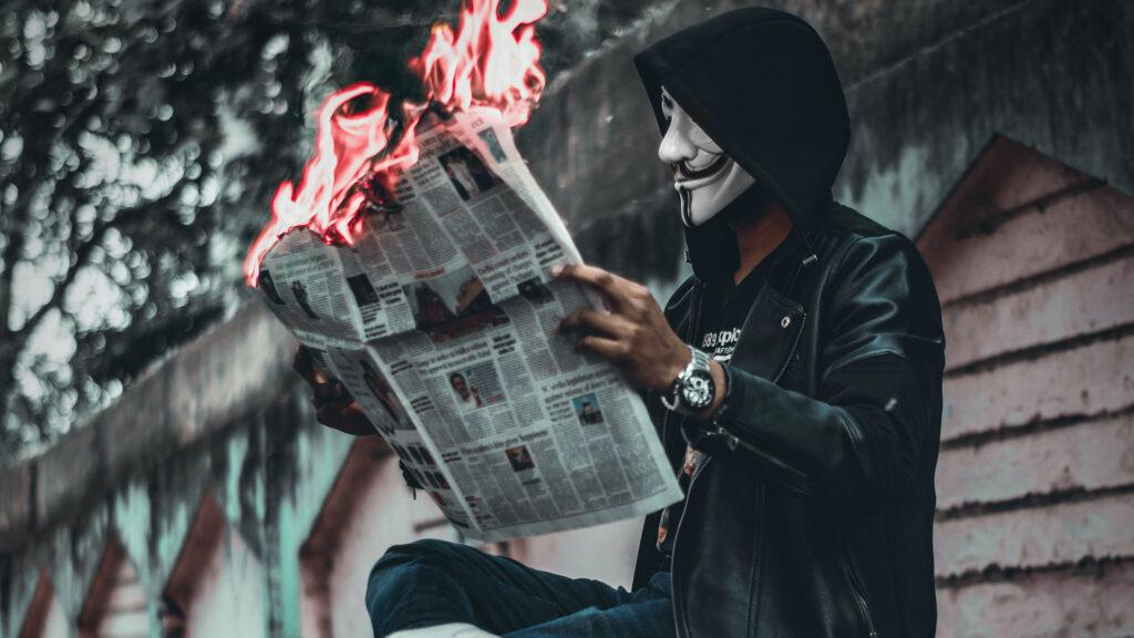 Maskierter Mann der eine brennende Zeitung liest.
