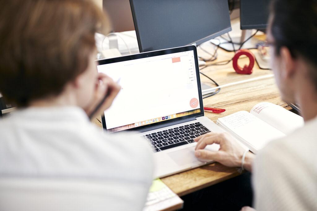 Zwei Personen arbeiten an einem Laptop